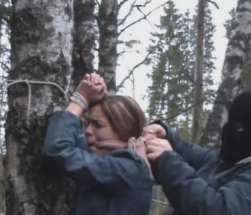 tied to a tree and gagged tightly by a hooded captor