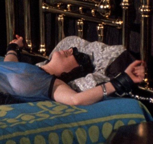 Annie Sprinkle tied to a four-poster brass bed