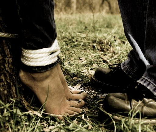 barefoot woman bound by man wearing hiking boots