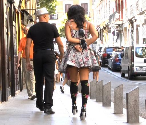 walking down a european city street with her arms tied behind her back