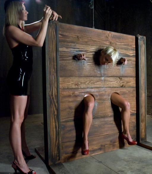 Locking her slave Vendetta into the bondage wall stocks