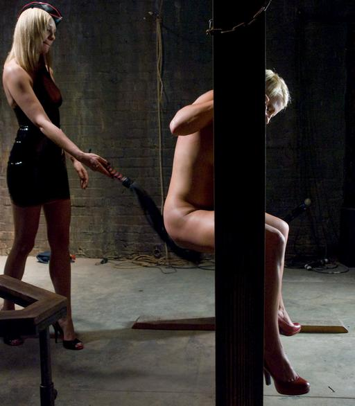 whipping the ass of the girl locked in the bondage wall stocks