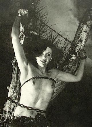 topless B movie starlet chained to a tree