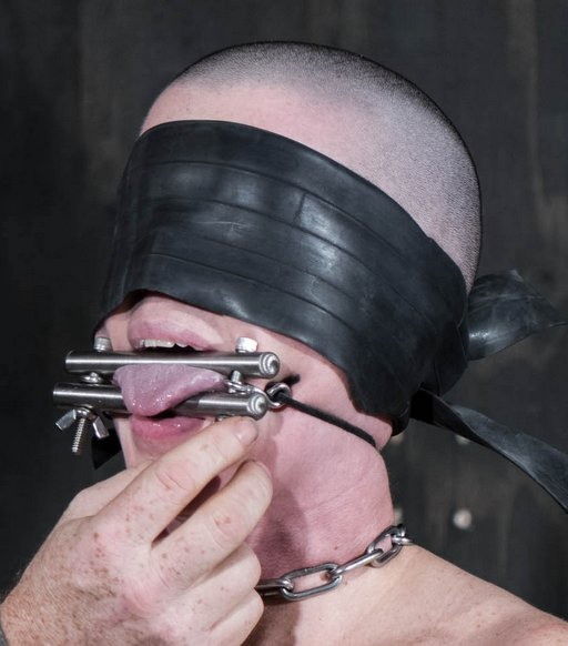 tongue bondage for a slave with a shaved head and a blindfold