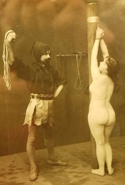 vintage erotica photo of a naked woman tied to a post for a flogging with ropes