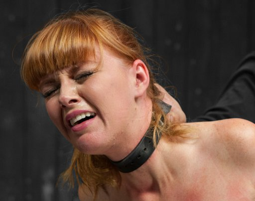 bondage redhead with a suffering look on her face