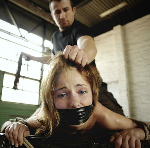 gagged girl getting her hair pulled during a brutal bondage whipping
