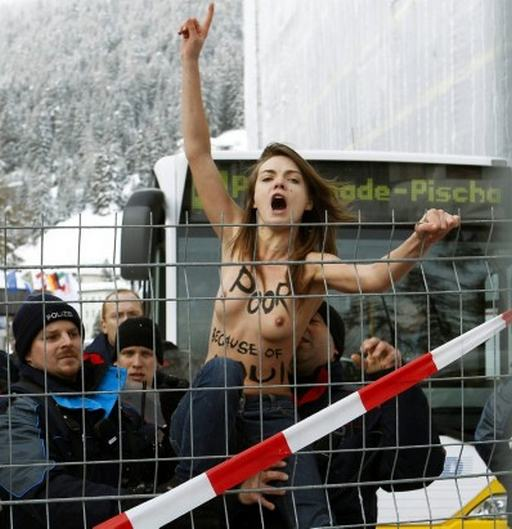 naked protester climbing a fence at davos protest