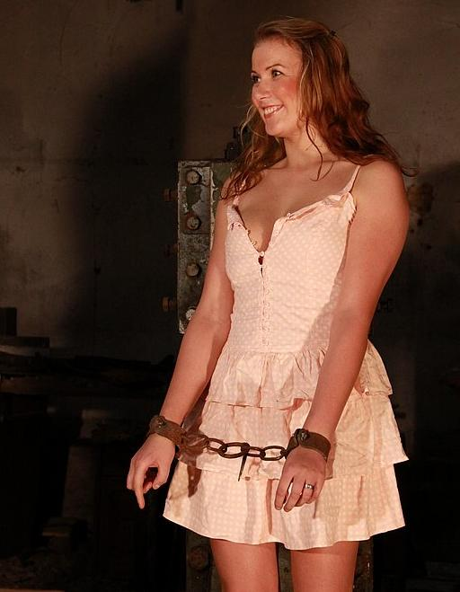 manacled girl grinning before her whipping