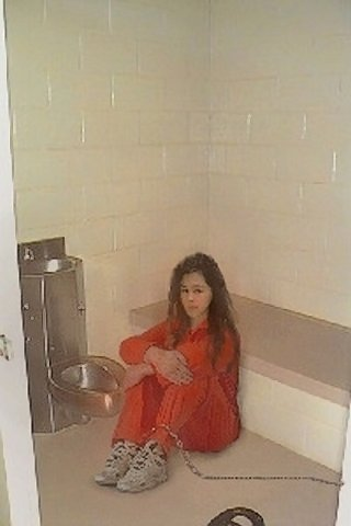 ankle chained prisoner in prison jump suit next to a prison toilet