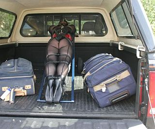 bondage girl on hand cart and loaded into back of pickup with two big suitcases