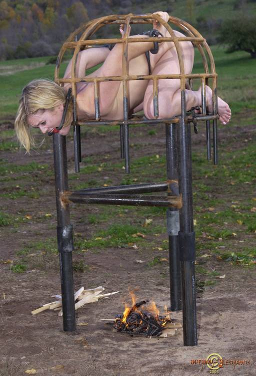 slavegirl in an iron cage over a burning camp fire