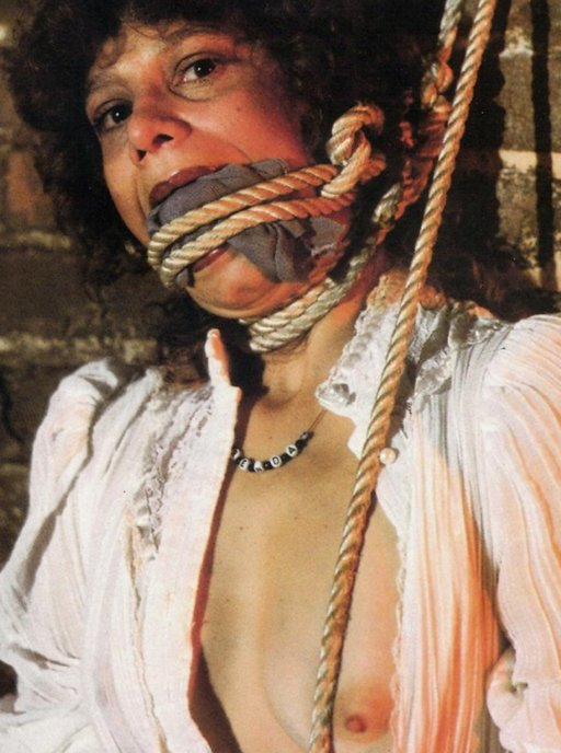 cloth gagged and roughly tied against a brick wall with course ropes