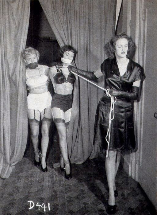 womn leads two bound and gagged women in lingerie