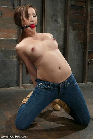 gagged woman hogtied on her knees with her jeans still on