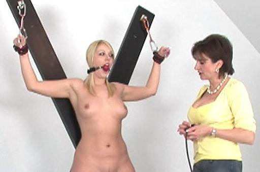 crucified blonde watches apprehensively as her mistress sets the controls on the fucking machine in her pussy