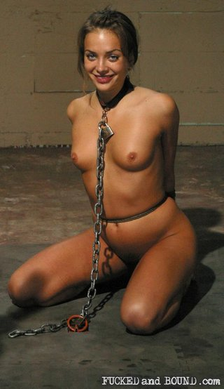 nika noire chained on her knees and smiling a delicious come-hither smile