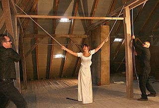 whipping girl tied with ropes to overhead beams