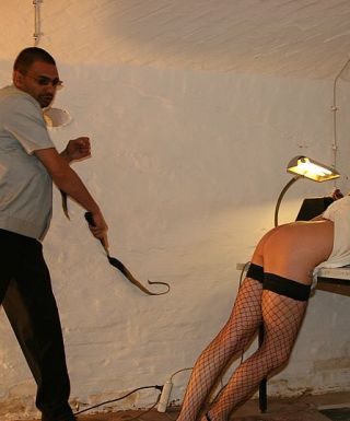 girl in straightjacket whipped over the wardens desk in whipping prison