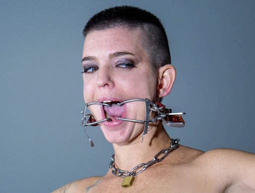 buzz cut woman wearing dental gag and padlocked chain collar