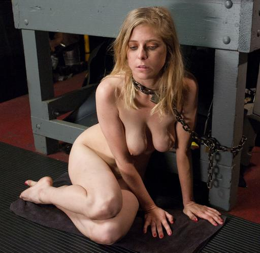 penny pax chained to a bench in a filthy auto shop