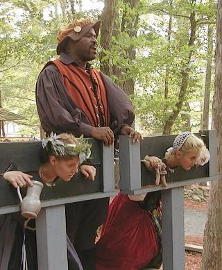 jailor contemplating some butt sex with the wenches in his pillory