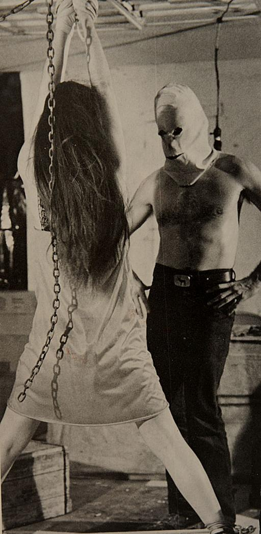 captive woman tied up by a man wearing a pillow case with eye holes caught in it