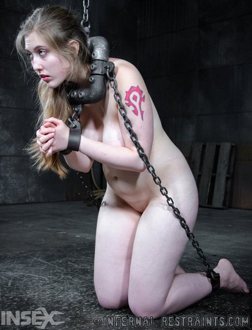 kneeling in chains and held in place with heavy iron pipe collar