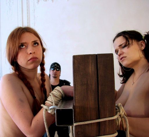 two girls being whipped while tied to a wooden post