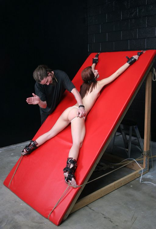 spanked on a red leather bondage wall