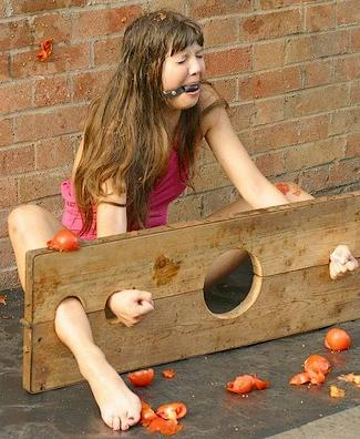 rotten tomatoes in the face for the gagged girl in the stocks
