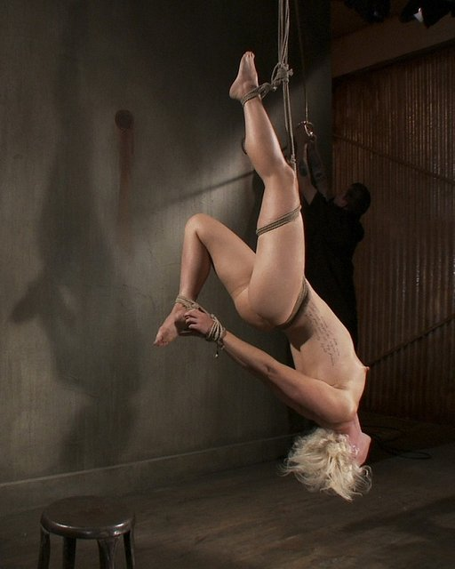 Tall blonde Dylan Ryan in heavy suspension bondage at Sadistic Rope