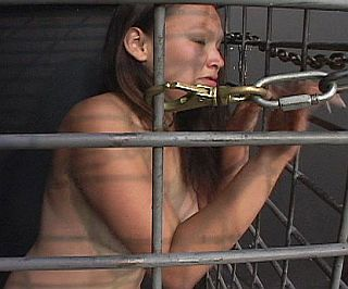 unhappy girl in steel dungeon cage