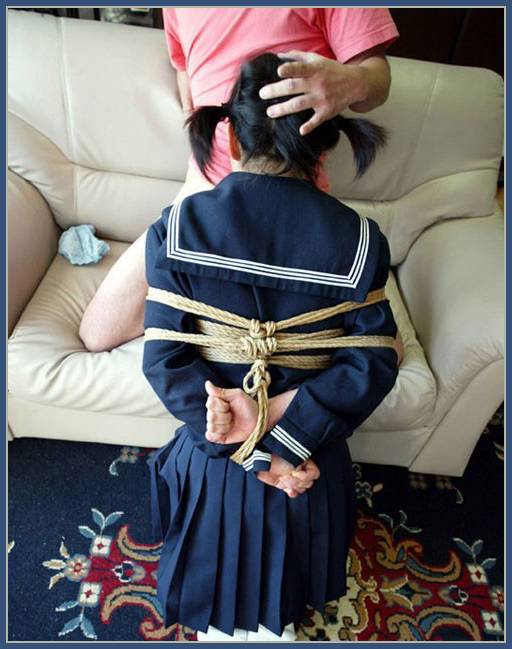 woman in japanese schoolgirl outfit giving a bondage blowjob