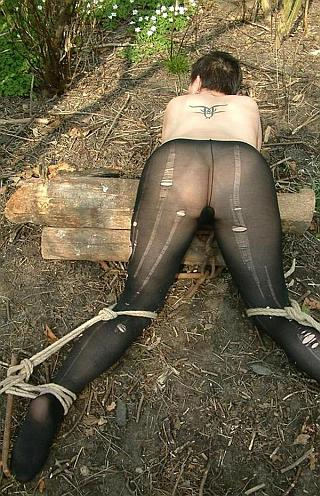 staked out over some logs for bondage sex