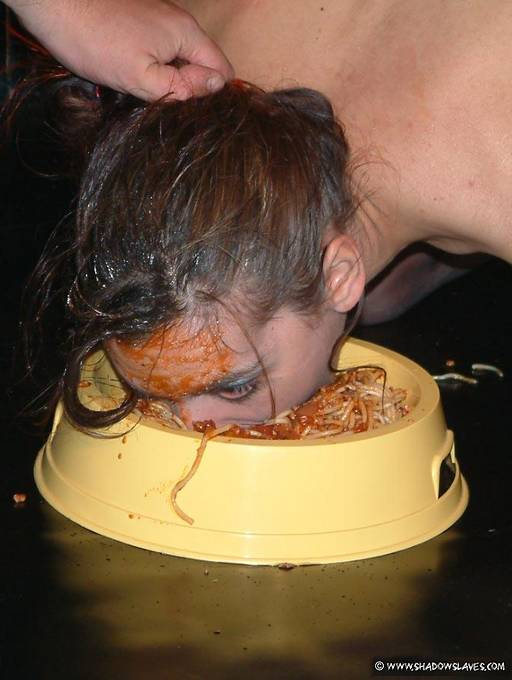slave girl eating spaghetti out of a dog dish with her mouth and face