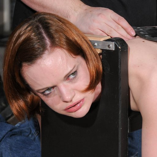 rebellious looks from Hazel Hypnotic as she is punished in the locking spanking bench