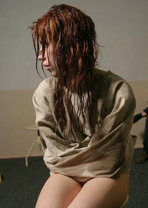 wet woman in a prison straitjacket