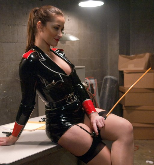 Dani Daniels in her sexy rubber interrogator costume, with rattan cane