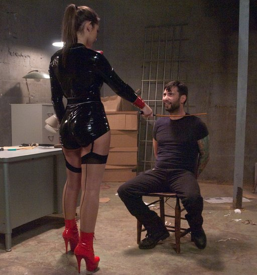 Dani Daniels menacing a virile male captive.  Only his hands aren't tied property to the chair or behind his back