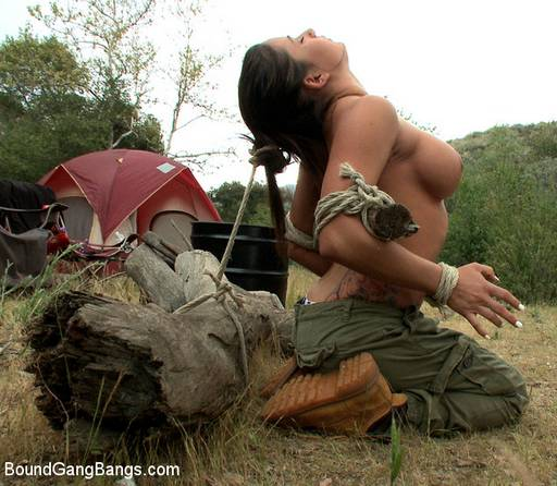 tied to a fallen log outside her camping tent with her boobs exposed for all to see