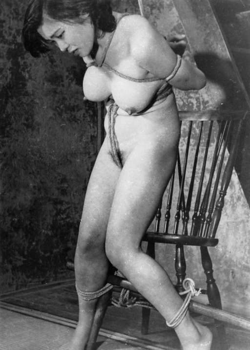 woman tied with rope and a heavy wooden dowel in vintage Japanese rope bondage
