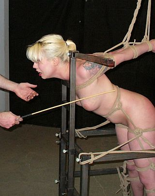 anguished blonde in bondage and about to get her titty caned