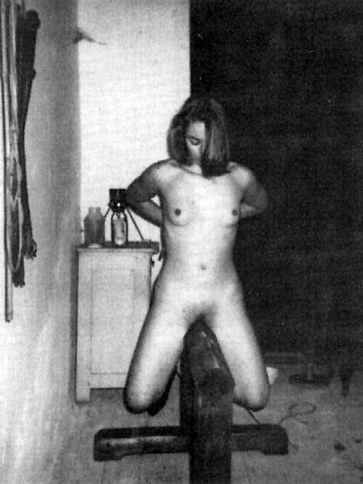 naked woman riding a painful wooden beam